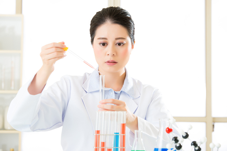 boundaries: asian female scientist Breaking scientific boundaries with her research use dropper in Laboratory Stock Photo