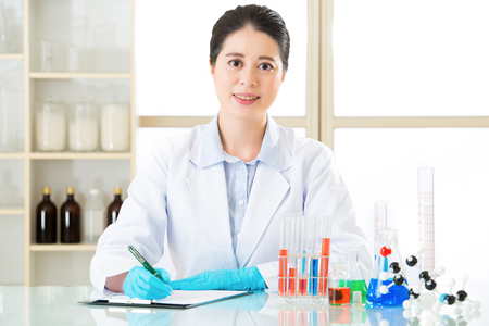 pathologist: Asian female scientist recording research data with smile face in laboratory