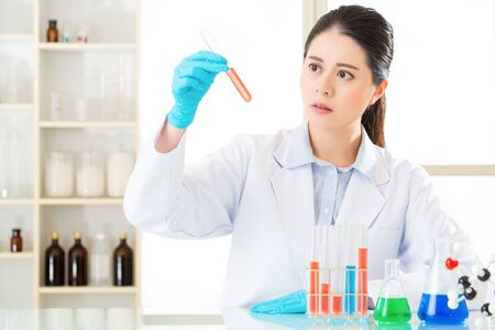 frontiers: Asian female forensic scientist braving new medical frontiers on chemicals in laboratory Stock Photo