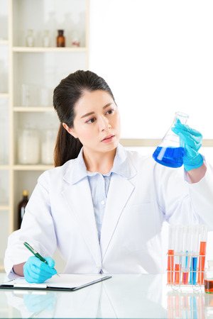 pathologist: Asian female scientist recording her research data write on clipboard in laboratory Stock Photo