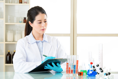 forensic science: Asian female scientist recording her research data write on clipboard in laboratory Stock Photo