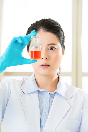 frontiers: female scientist Braving new medical frontiers bottle with red liquid Stock Photo