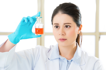 antidote: Asian female scientist Exploring new medical frontiers antidote in bottle