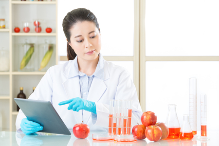 genetic food modification: Asian female scientist touch the digital tablet to research for genetic modification food Stock Photo