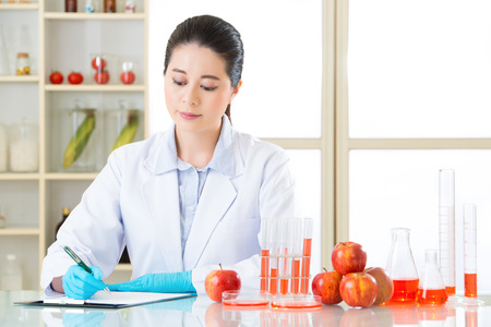 modification: Asian female scientist Recording her data is important for genetic modification