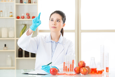 apple gmo: Asian female scientist drop the cure for genetic modification in laboratory Stock Photo