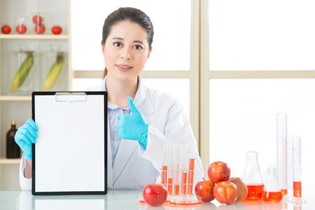apple gmo: thumb up for good genetic modification food test record on clipboard