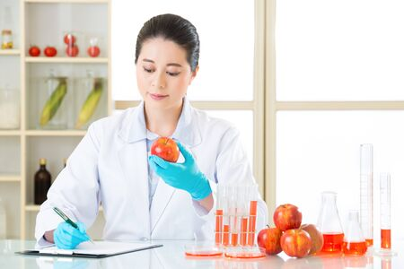 Recording data of test result from Examining genetic modification in laboratory Stock Photo