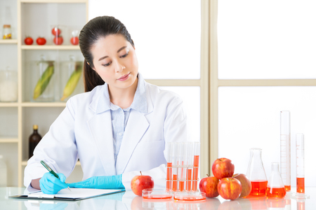 apple gmo: Asian female scientist recording research data for genetic modification test