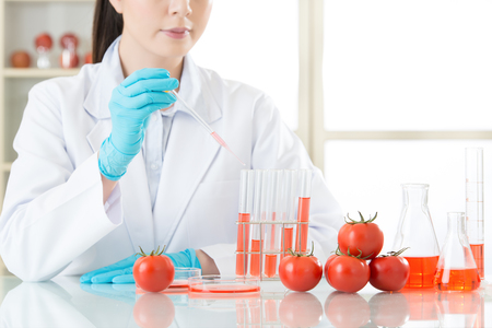 Asian female scientist drop the cure for genetic modification in laboratory Stock Photo