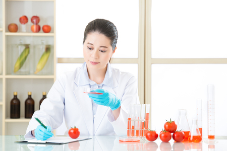 Asian female scientist thinking and holding an tomato for genetic modification food Stock Photo