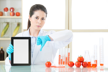 genetic food modification: genetic modification food are bad for human health by digital tablet Stock Photo