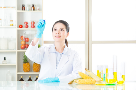 genetically modified crops: Asian female scientist recording the result on writing glass in laboratory Stock Photo