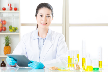 yellow notepad: Asian female scientist touch the digital tablet holding soya bean in laboratory Stock Photo