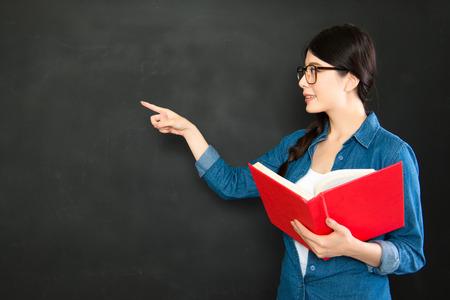 Présentation de l'étudiant asiatique son travail avec des lunettes et un livre de texte debout devant le tableau noir Banque d'images - 61192908