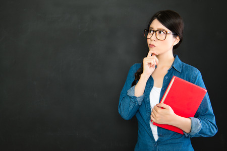 university student thinking about question of assignment in front of blackboard Stock Photo