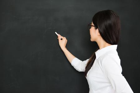 良いアジアの教師が教室でチョークで黒板に書く 写真素材