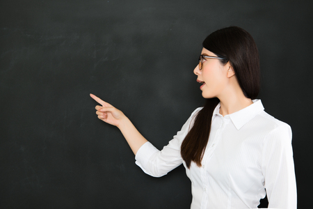 young asian teacher pointing a question on blackboard in school