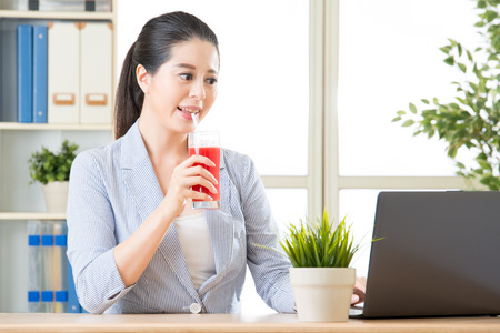 use computer: asian business woman drinking watermelon juice and use computer for business