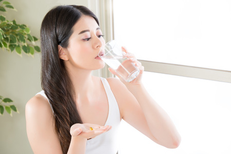 beautiful asian women drinking water eat nutritional supplement pill at home Stock Photo