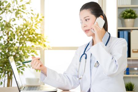 의사는 스마트 폰 및 컴퓨터, 의료 및 의학 개념, 병원 사무실 배경에 의해 환자의 상태를 설명