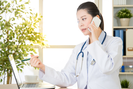 Doctor explain patients condition by smart phone and computer, healthcare and medicine concept, hospital office background Imagens