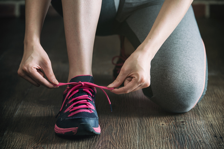 shoestring: knee down with tie sneakers shoestring before fitness exercise, gym sport healthy lifestyle