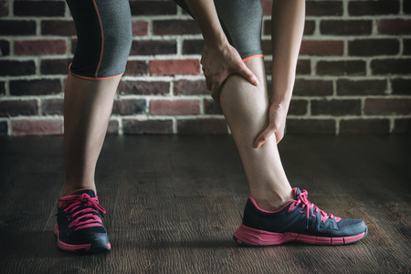 calf strain: have a leg cramp in fitness exercise training, healthy lifestyle concept, indoors gym wooden floor brick wall background