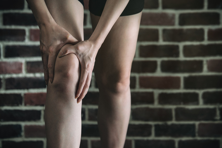 calf strain: her knee feel painful after fitness exercise, healthy lifestyle concept, indoors gym wooden floor brick wall background