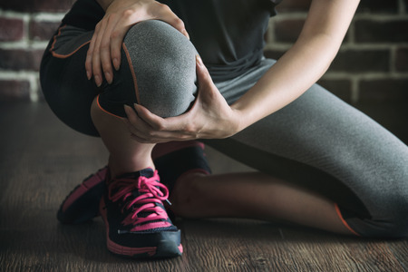 her knee feel painful after fitness exercise, healthy lifestyle concept, indoors gym wooden floor brick wall background