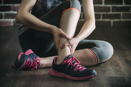 her ankle injured in gym fitness exercise training, healthy lifestyle concept, indoors wooden floor brick wall background