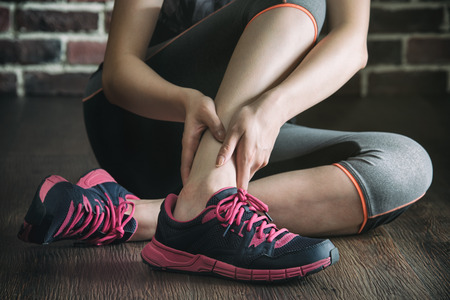 calf strain: her ankle injured in gym fitness exercise training, healthy lifestyle concept, indoors wooden floor brick wall background