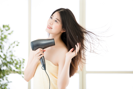 beautiful woman blowing the wind by hair dryer after shower, indoors background