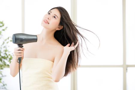 Asiatiques beauté femme cheveux sèche pour sécher les cheveux après la douche, fond intérieur Banque d'images - 65073146