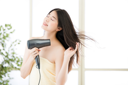 asian beauty woman hair dryer to drying hair after shower, indoors background