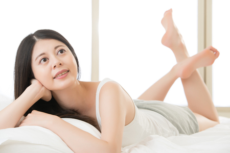 blissfully: beautiful smile Asian woman lying on bed comfortably and blissfully in the morning, bedroom background