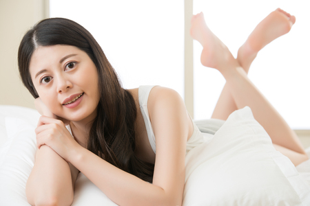 blissfully: beautiful Asian young woman lying on bed comfortably and blissfully in the morning, bedroom background