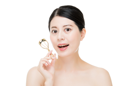 curler: beautiful fashion girl holding eyelash curler makeup accessory. asian beauty concept. isolated on white background