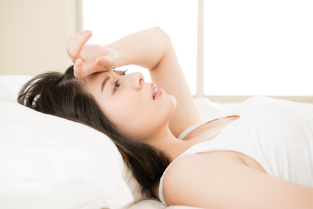 sit down: beautiful asian woman feel unwell sickness and ill lying on bed at home, bedroom background Stock Photo