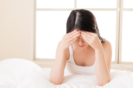 Beautiful asian woman suffering headache painful and massage forehead sit on bed. bedroom background
