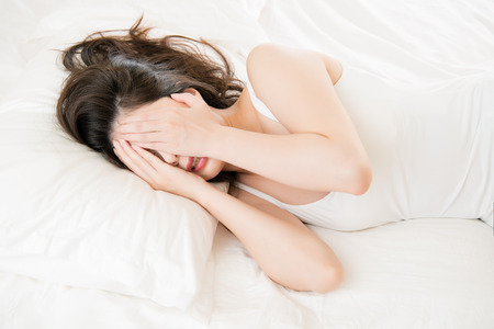 beautiful asian woman feel unwell painful and ill lying on bed at home, bedroom background