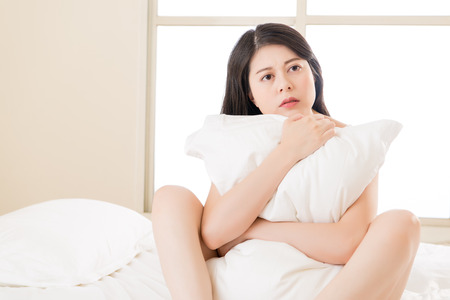 asian beautiful woman feel unwell sickness sit on bed. bedroom background