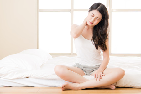 Beautiful asian woman suffering Shoulder neck ache tired sit on bed. bedroom background Stock Photo