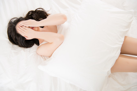 beautiful asian woman feel unwell painful and holding pillow on bed at home, bedroom background Imagens