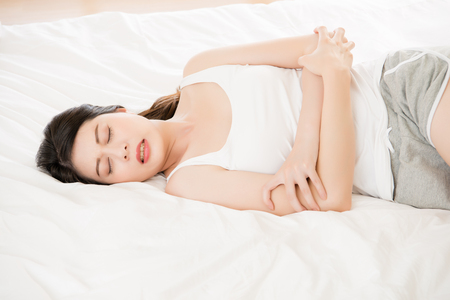 menstruation period: Beautiful asian woman suffering from stomach pain at home on bed, bedroom background, menstruation period concept Stock Photo