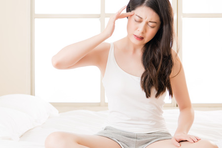 Beautiful asian woman suffering headache and massage forehead sit on bed. bedroom background