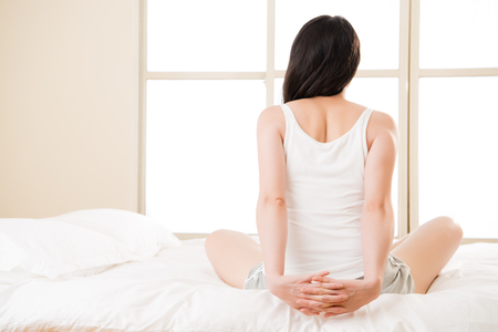 asian woman stretches back pain backache, spinal or lower back problem. bedroom background Stock Photo