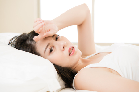 beautiful asian woman feel unwell sickness and ill lying on bed at home, bedroom background Stock Photo