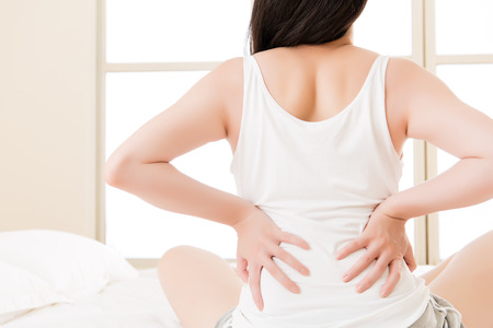 asian woman suffers from back pain backache, spinal or lower back problem. bedroom background
