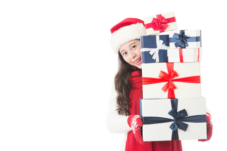 christmas spending: Christmas shopping asian woman holding many Christmas gifts in her arms wearing santa hat and winter clothing. Beautiful young female model isolated on white background.